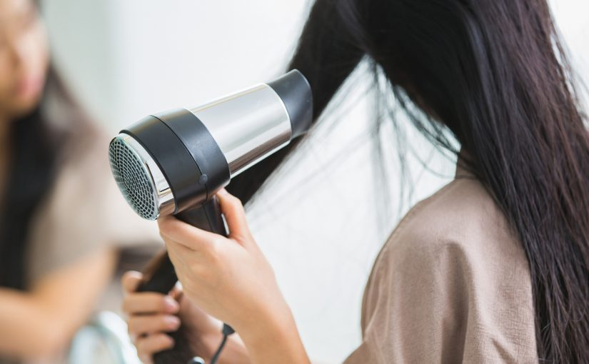 woman-using-portable-hair-dryer